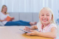 Little girl using tablet pc in the living room while her mother is reading a book Royalty Free Stock Image