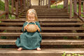 little girl in vintage retro linen dress barefoot sitting on a wooden stairs in the park looking into Wicker basket Royalty Free Stock Photo