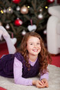 Little girl waiting for the christ child cute happy smiling awaiting arrival of lying on a carpet at foot of christmas tree Royalty Free Stock Images