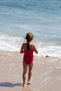 Little Girl Walking into the Ocean on the Beach Royalty Free Stock Photography