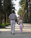 Little girl walking in a park with her grandfather Royalty Free Stock Photo