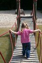 Little girl walking on a suspended wooden bridge back view Royalty Free Stock Images