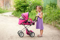 Little girl walking with toy stroller little mama a Royalty Free Stock Images
