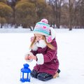 Little girl warms hands on candle in lantern Royalty Free Stock Photo