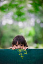 Little girl was hiding behind a chair in the park Stock Image