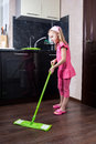 Little girl washes floor with a mop Royalty Free Stock Photo