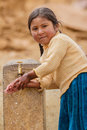 Little girl washig hands andean from the region of potosí in bolivia using a recently installed water supply in her small town Royalty Free Stock Images
