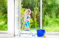 Little girl washing a window cute laughing curly toddler big with squeegee in beautiful white living room with door into the Royalty Free Stock Photo