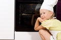 Little girl watching her homemade pizza cook Royalty Free Stock Photo