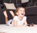 Little girl watching tv happy cute holding a remote control Stock Image
