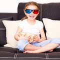 Little girl watching tv with popcorn d Royalty Free Stock Image