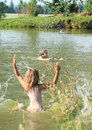 Little girl in water standing pond and splashing the on a boy Stock Photography