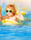 Little girl on water swing closeup portrait of cute baby swinging attractions in aquapark wearing sunglasses red heart cheek Stock Image
