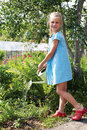 Little girl watering the flowers in the family garden at a summe summer day Royalty Free Stock Photo