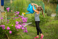 Little girl watering the flowers near the country house. Hobby. Royalty Free Stock Photo