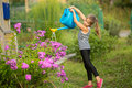 Little girl watering the flowers near the country house. Summer. Royalty Free Stock Photo