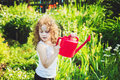 Little girl watering a plant with watering can.