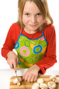 Little girl wearing apron slicing mushrooms Stock Photo