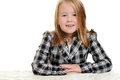 Little girl wearing checkered jacket sitting at table Royalty Free Stock Photos