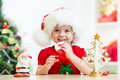 Little girl wearing a festive red Santa hat with Royalty Free Stock Photo