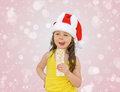 Little girl wearing red santa hat eating white chocolate Stock Image