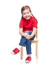 Little girl wearing red t-short and posing on chair Royalty Free Stock Images