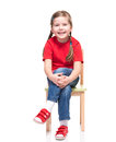 Little girl wearing red t-short and posing on chair Stock Images