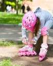 Little girl is wearing roller blades in city park Stock Photography