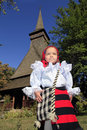 Little girl wearing Romanian traditional clothing and traditional wood church on a background Royalty Free Stock Photo