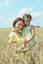 Little girl in a wheat field with his mother Royalty Free Stock Photo