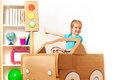 Little girl at the wheel of handmade cardboard car Royalty Free Stock Photo