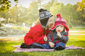Little girl whispers a secret to baby brother outdoors her wearing winter coats and hats sitting at the park Royalty Free Stock Photo