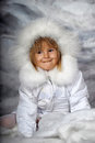 Little girl in a white fur coat and hat on winter background Royalty Free Stock Photography