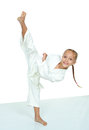 A little girl in a white kimono beat punch leg hits kick Royalty Free Stock Photo