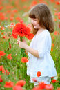 Little Girl with wild red flowers in the field Royalty Free Stock Photo