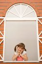 Little girl in the window smiling with pigtails looking out Royalty Free Stock Photography