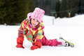 stock image of  Little girl in winter outfit fell while skiing.
