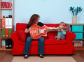Little girl and woman play with electric guitar Stock Photos