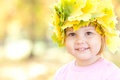 Little girl in a wreath of maple leaves in autumn fore Royalty Free Stock Photos