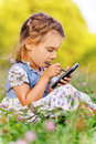 Little girl writes stylus on device Stock Images