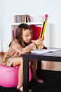 Little girl writing with a giant pencil at her home Royalty Free Stock Photo