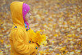 Little girl in yellow coat collects yellow maple leaves pretty smiling with pink cap autumn city park Stock Images