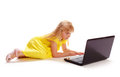 Little girl in a yellow dress lying on white background and playing computer Stock Photos