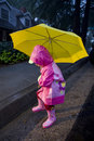 Little girl with yellow umbrella playing in rain 1 Royalty Free Stock Photo