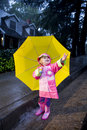 Little girl with yellow umbrella playing in rain 3 Stock Image