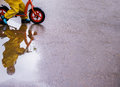 Little girl in yellow waterproof clothes with bike near a puddle Royalty Free Stock Photo