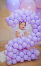 Little girls birhtday girl looking from two shape of lilac balloons Stock Photos