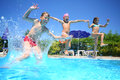 Little girls and boy fun jumping into the swimming pool Royalty Free Stock Photo