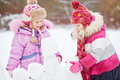 Little girls build wall from snow blocks in winter park Royalty Free Stock Image
