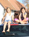 Little girls on a car barefoot kids sitting silver with roof behind Stock Photography
